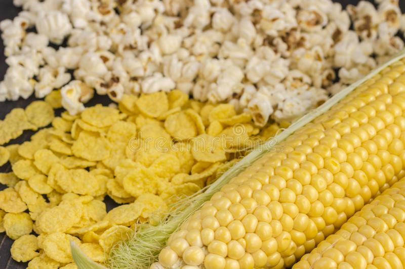 Raw corn cob, popcorn and cornflakes, top view royalty free stock photos