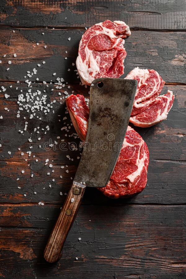 Raw cowboy steak and Chuck eye roll with seasonings on old butchery wood background, prime rib. Nobody stock images