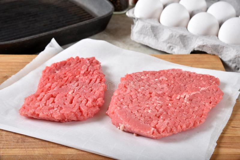 Raw cube steaks. Uncooked cube steaks on a cutting board near a cast iron grill and a carton of eggs royalty free stock photo