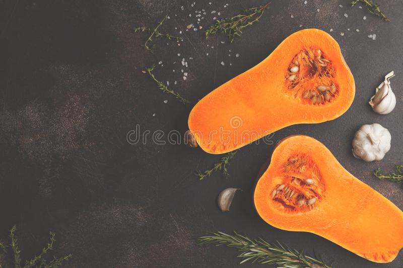 Raw cut pumpkin batternat with rosemary, thyme and garlic on a d stock images