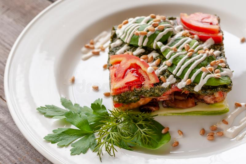Vegetarian dish: lasagna with zucchini, mushrooms, tomatoes, basil, wheat germ, spinach, garlic. Raw food dish. royalty free stock photography