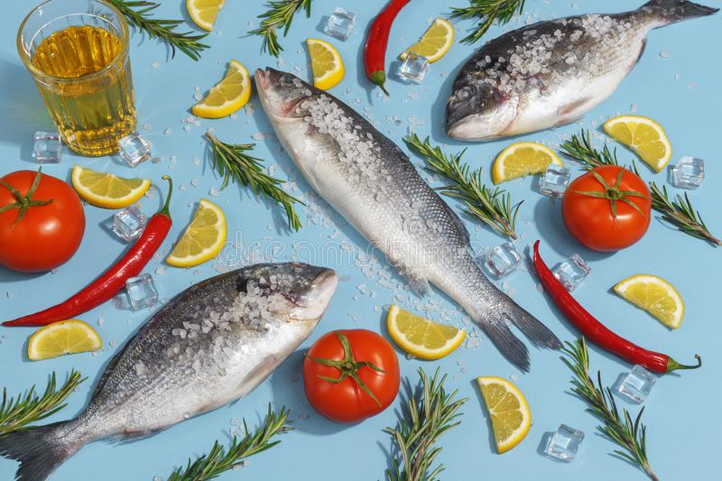 Raw dorada fish with spices, salt, lemon and herbs, rosemary on a ligth-blue background. Top view royalty free stock image