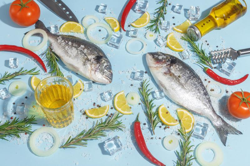 Raw dorada fish with spices, salt, lemon and herbs, rosemary on a ligth-blue background. Top view. Seafood healthy freshness pepper eating bream dorado dinner stock photography