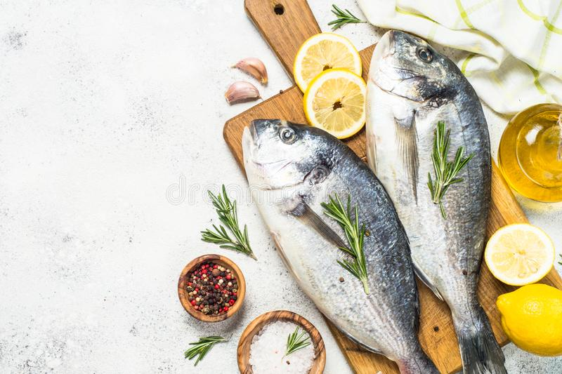 Raw dorado fish on cutting board on the table. Dorado fish on cutting board on white stone table with ingredients for cooking. Top view with space for text royalty free stock photography