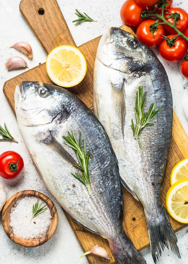 Raw dorado fish on cutting board on the table. Fresh fish dorado on cutting board on white stone table with ingredients for cooking. Top view royalty free stock image