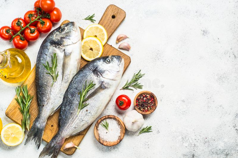 Raw dorado fish on cutting board on the table. Fresh fish dorado on cutting board on white stone table with ingredients for cooking. Top view with copy space royalty free stock image