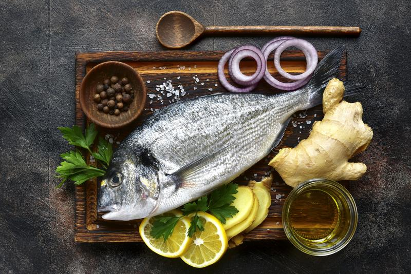 Raw dorado fish with ingredients for making.Top view. stock photography