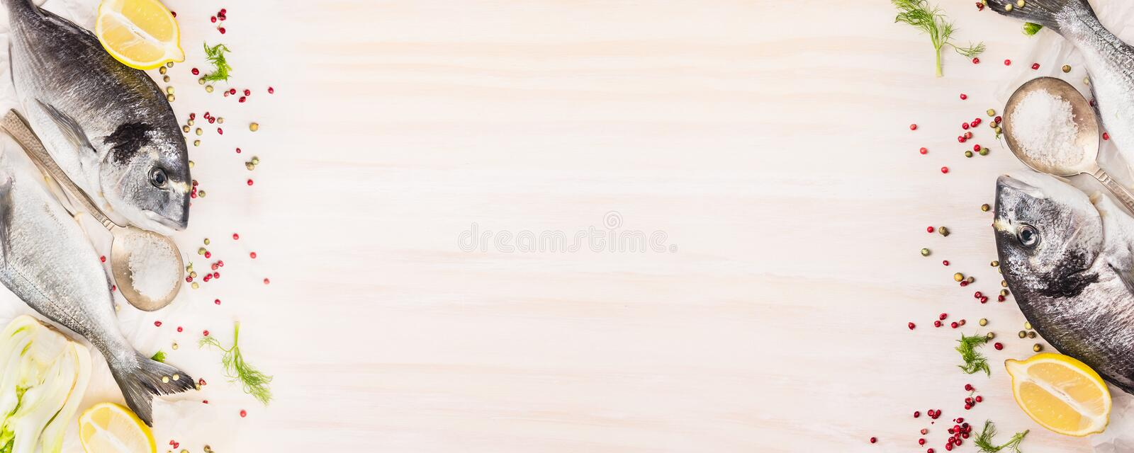 Raw dorado fish with lemon, herb and spices on white wooden background, top view, banner for website with cooking concept, royalty free stock photos