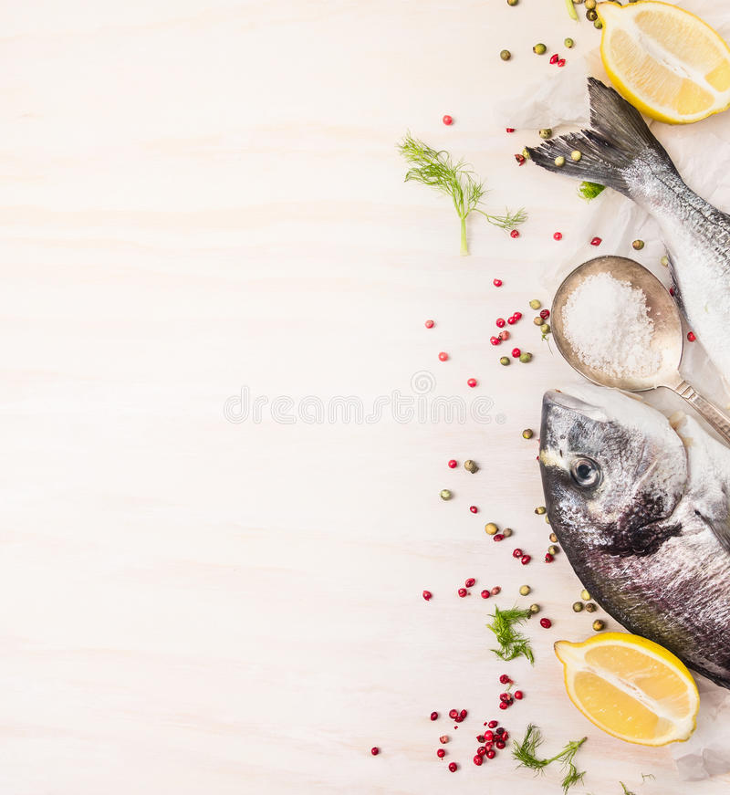 Raw dorado fish with multicolor pepper,lemon an spoon of salt on white wooden background, top view royalty free stock image