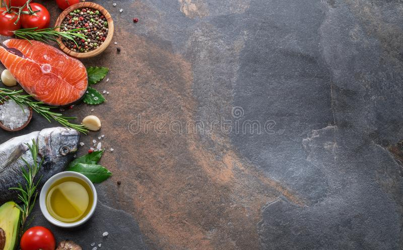 Raw dorado fish and salmon steak with spices and vegetables on the graphite board. Top view stock images