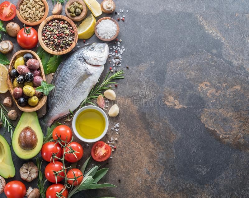 Raw dorado fish with spices and vegetables on the graphite board. Top view stock photos