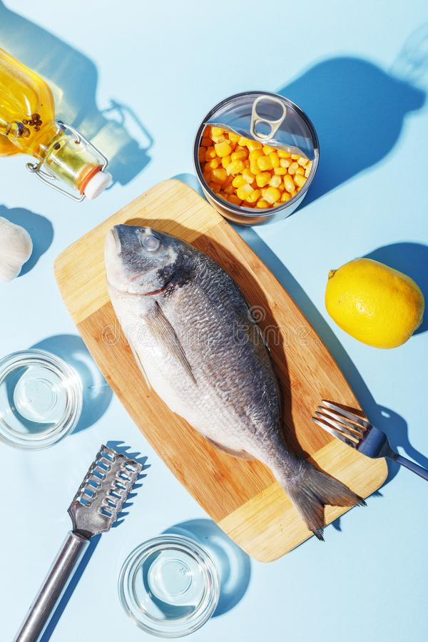 Raw dorado fish on a wooden board, ingredients for cooking and spices on a blue background. Delicious dinner food meal bream seafood table mediterranean fresh royalty free stock photo