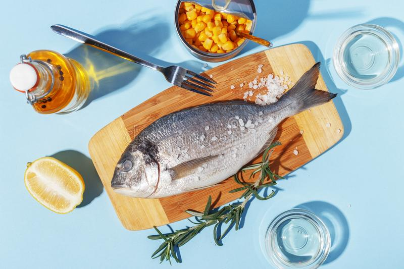 Raw dorado fish on a wooden board, ingredients for cooking and spices on a blue background. Delicious dinner food meal bream seafood table mediterranean fresh royalty free stock photos