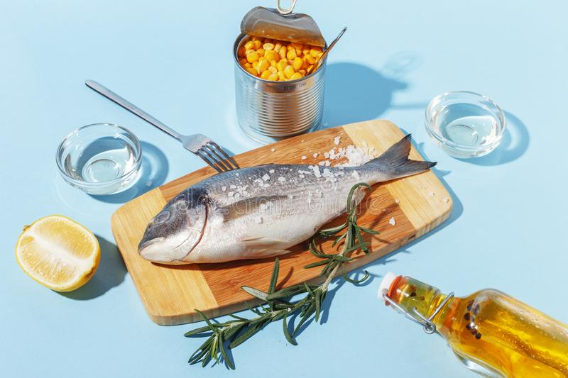 Raw dorado fish on a wooden board, ingredients for cooking and spices on a blue background. Delicious dinner food meal bream seafood table mediterranean fresh stock photography