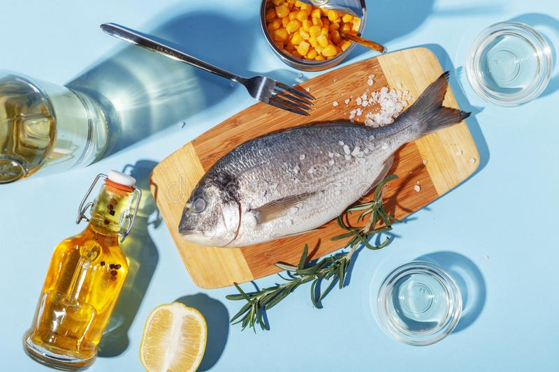 Raw dorado fish on a wooden board, ingredients for cooking and spices on a blue background. Delicious dinner food meal bream seafood table mediterranean fresh stock images