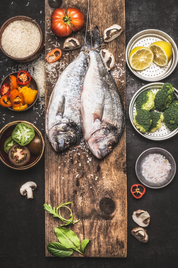 Raw dorado fishes and healthy cooking ingredients: rice, vegetables, lemon. stock image