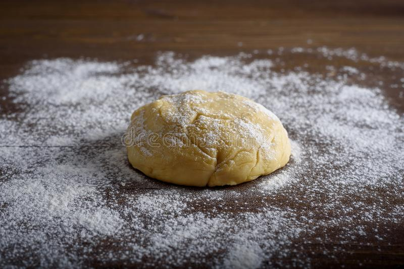 Raw dough ball sprinkled with white flour on a wooden table. stock photos