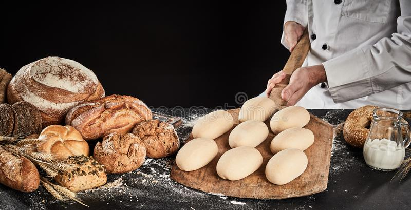 Raw dough for loaves of bread on a wooden paddle stock photos