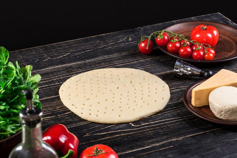 Raw dough for pizza preparation with ingredient: tomato sauce, mozzarella, tomatoes, basil, olive oil, cheese, spices stock image