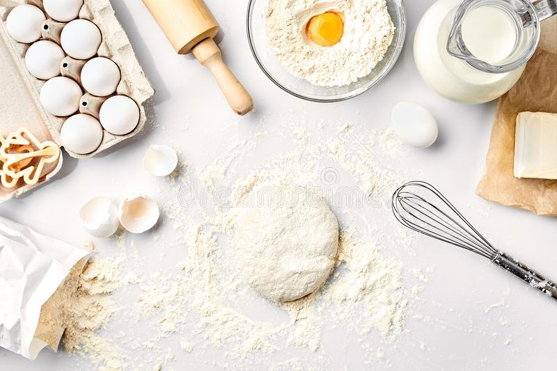 Raw dough ready for kneading on white table. Bakery ingredients, eggs, flour, butter. Shapes for making cookies. stock photography