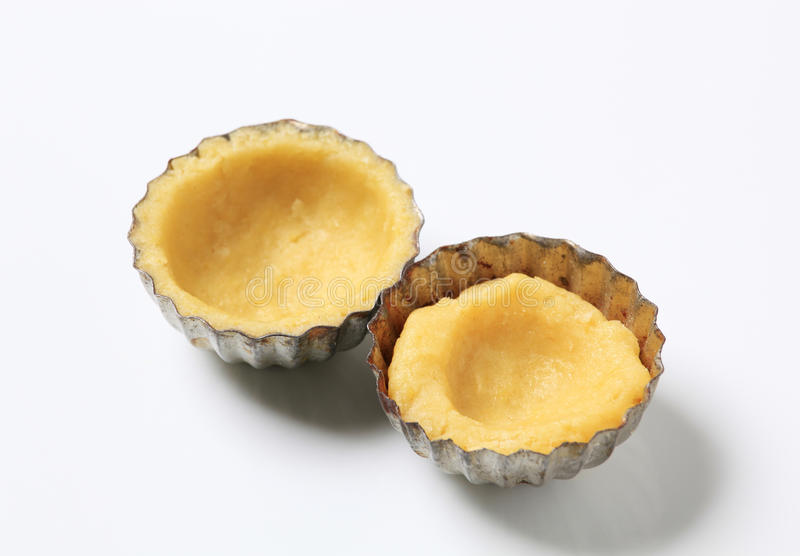 Raw dough in small tart pans stock photo