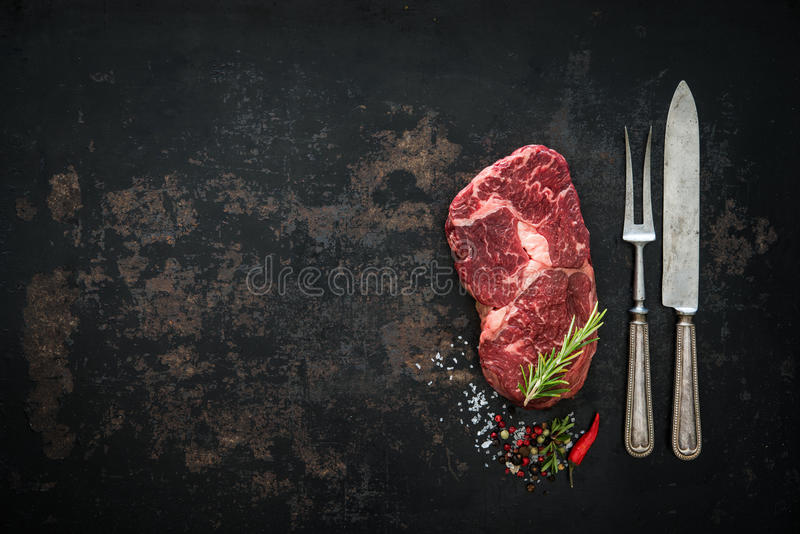 Raw dry aged beef ribeye steak. On dark background royalty free stock photos