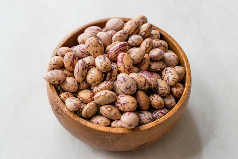 Raw Dry Pinto Beans on Marble Board with Wooden Bowl / Kidney Beans. stock photos
