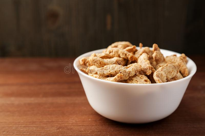 Raw dry soya meat chunks in a white bowl on a wooden table. View, vegan, textured, diet, food, health, healthy, ingredient, macro, natural, protein, vegetarian stock photo