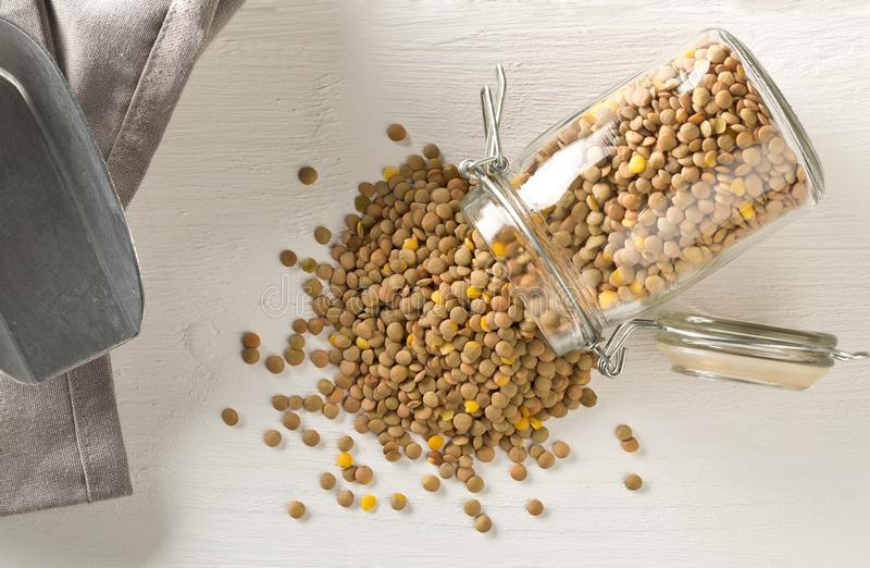 Raw, dry, uncooked brown lentil legumes in glass storage jar on white wood table background flat lay top view from above. Raw, dry, uncooked brown lentil legumes stock photo