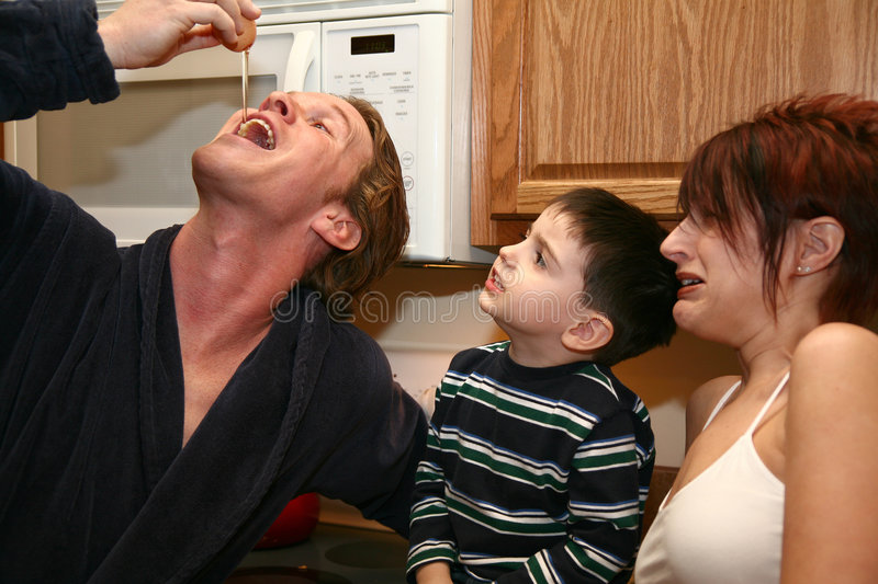 Raw Egg. Man grossing out family by eating a raw egg from the shell royalty free stock photos