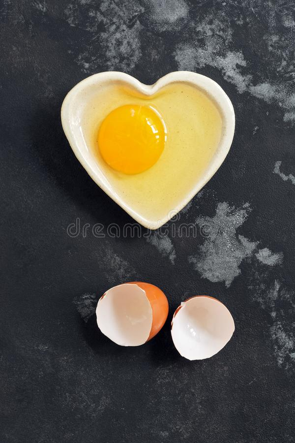 Raw egg broken in a bowl and eggshell on a dark concrete background. Flat lay royalty free stock image