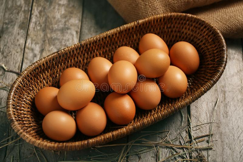 Raw eggs in basket on background. Raw eggs in basket on wooden background stock photos