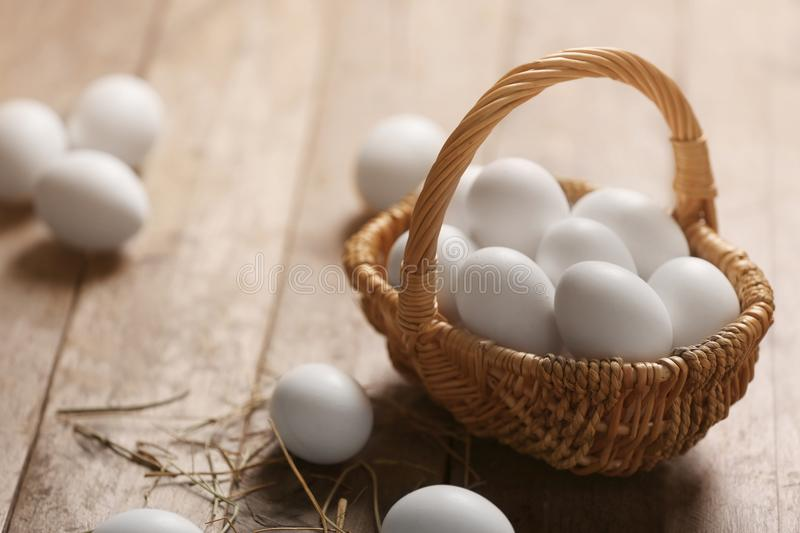 Raw eggs in basket. On wooden background royalty free stock photos