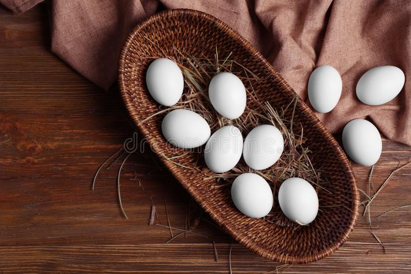 Raw eggs in basket on background. Raw eggs in basket on wooden background stock photo