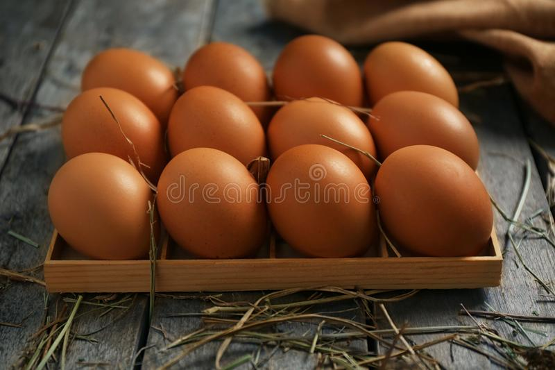 Raw eggs in box. On wooden background stock image