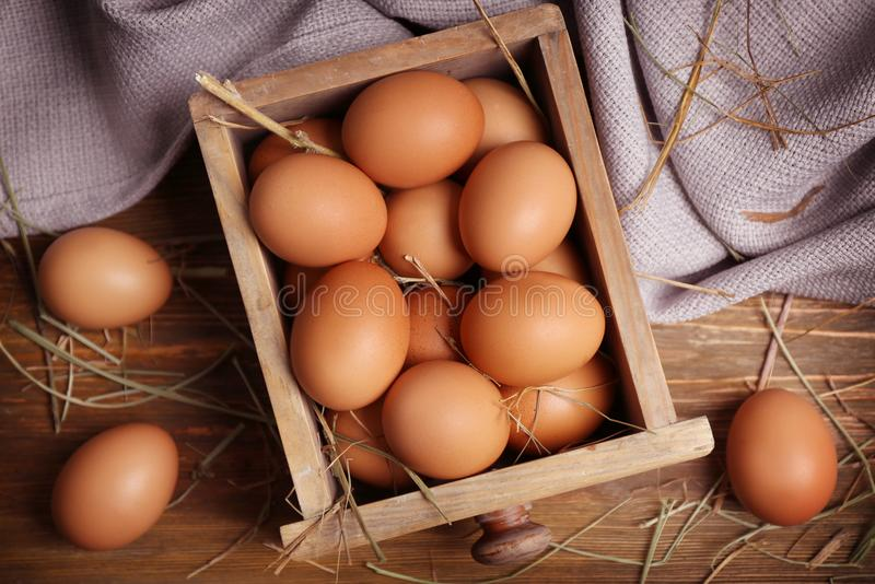 Raw eggs in drawer. On wooden background royalty free stock photos