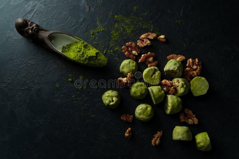 Raw energy balls with matcha tea powder on on dark background, top view. Horizontal image stock photo