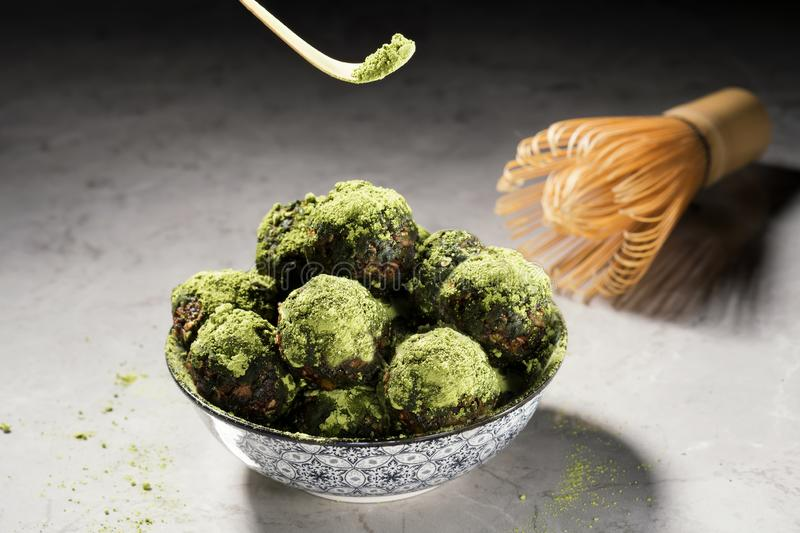 Raw energy balls with matcha tea powder on a grey marble background. Horizontal image, front view. Vegan sweet homemade dessert royalty free stock photography