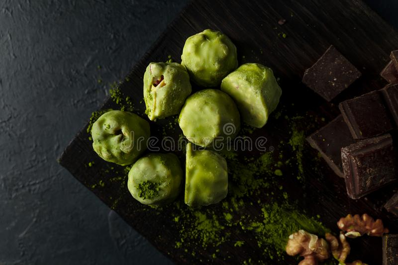 Raw energy balls with matcha tea powder on a wooden board on dark background. Horizontal image. Raw energy balls with matcha tea powder, walnuts, chocolate on a royalty free stock image