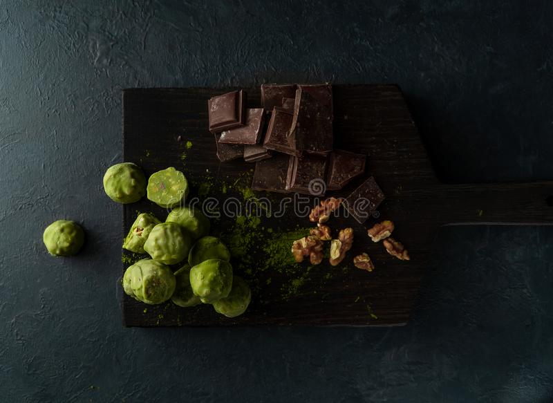 Raw energy balls with matcha tea powder on a wooden board on dark background. Horizontal image. Raw energy balls with matcha tea powder, walnuts, chocolate on a stock images