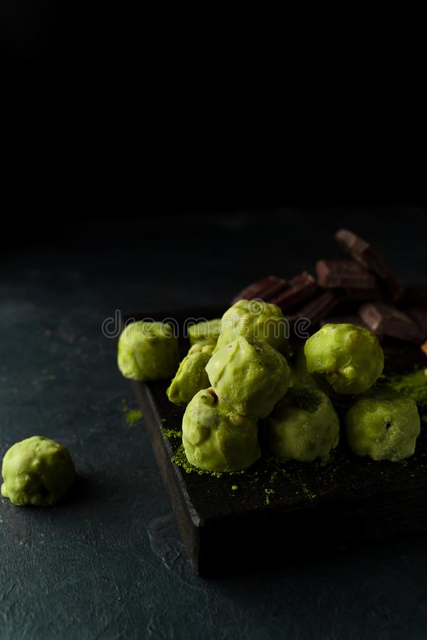 Raw energy balls with matcha tea powder on a wooden board on dark background. Vertical image. Raw energy balls with matcha tea powder, walnuts, chocolate on a stock photography