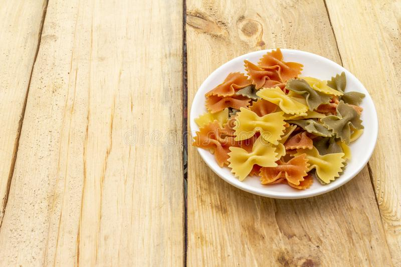 Raw farfalle multicolored pasta in white plate on wooden background. Preparing for children, top view, close up. Raw farfalle multicolored pasta in white plate stock photos