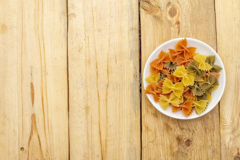 Raw farfalle multicolored pasta in white plate on wooden background. Preparing for children. Top view, close up royalty free stock photography