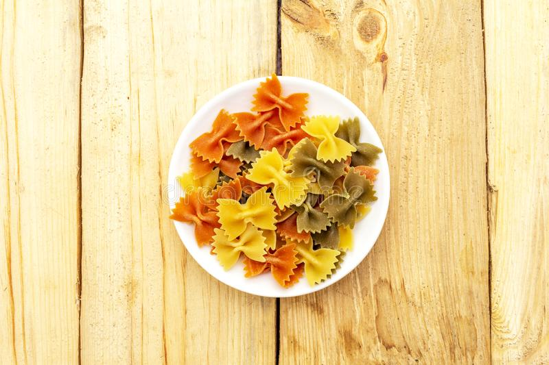 Raw farfalle multicolored pasta in white plate on wooden background. Preparing for children. Top view, close up stock photography