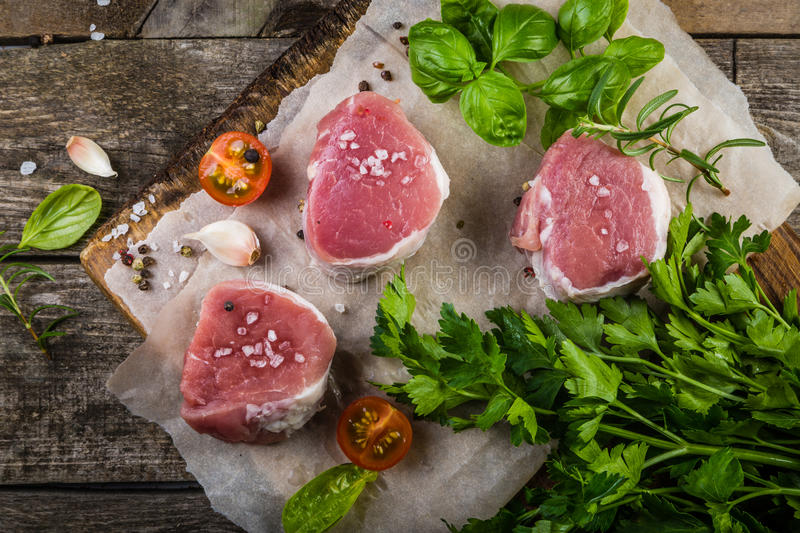 Raw filet mignon meat cuts with spice and herbs. Wood background stock image