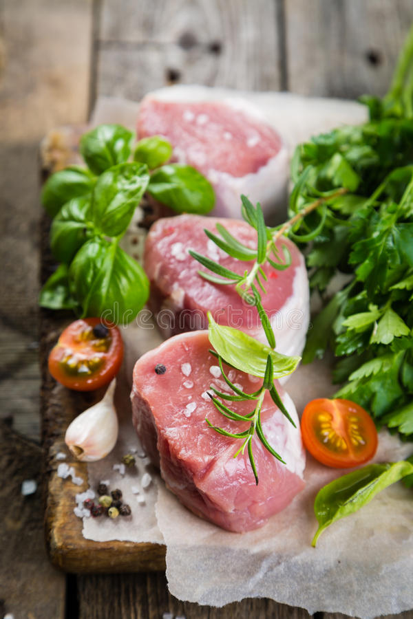 Raw filet mignon meat cuts with spice and herbs. Wood background royalty free stock images