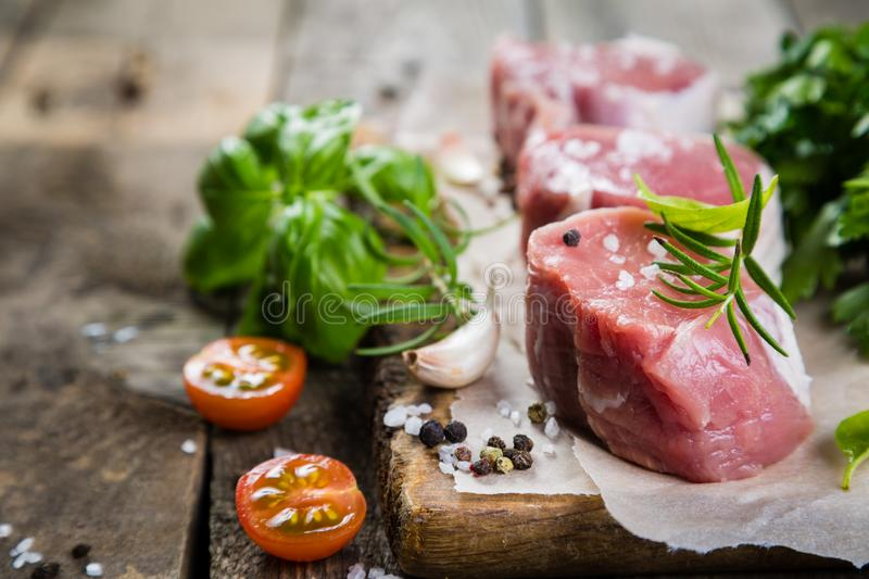 Raw filet mignon meat cuts with spice and herbs. Wood background stock images