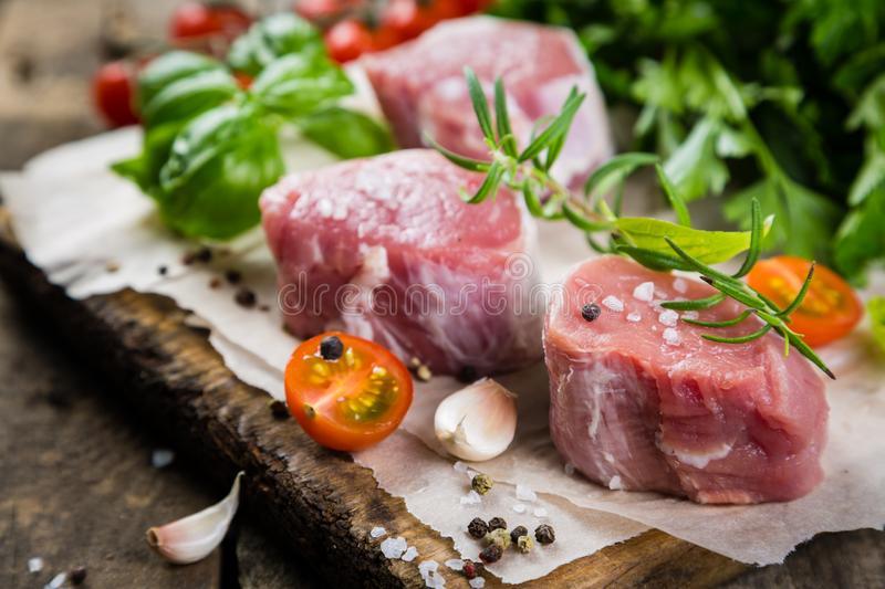 Raw filet mignon meat cuts with spice and herbs. Wood background royalty free stock photo