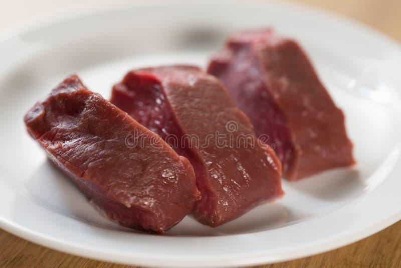 Raw filet mignon steaks on white plate. Closeup photo royalty free stock image