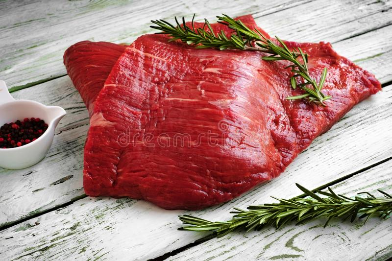 Raw fillet of beef brisket on white wooden background. With salt, rosemary and pepper royalty free stock photo